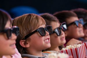 Group of children at the cinema watching a 3D movie